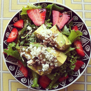 Microgreens in a salad of strawberries, avocado, spring greens and feta. Topped with tangerine balsamic.